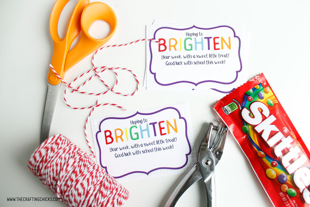 Scissors, Brighten your day printable gift tag, baker's twine, hole punch and Skittles to make Brighten Your Day gift