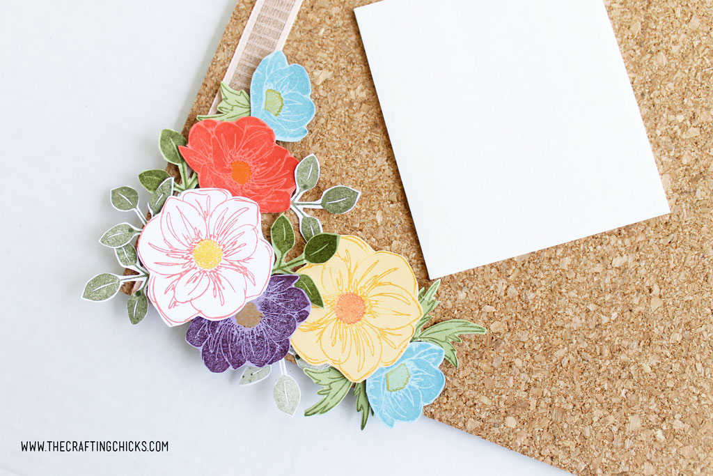 Stamped flowers layered on a cork board