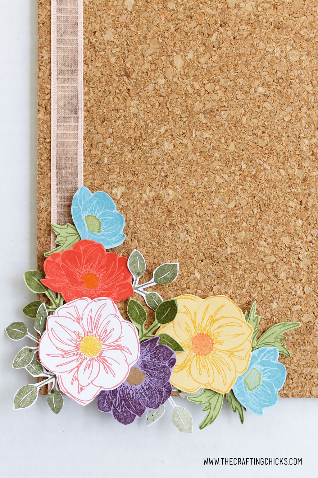 Layered stamped flowers on a cork board