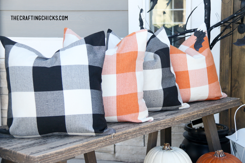 Plaid pillows on wooden bench