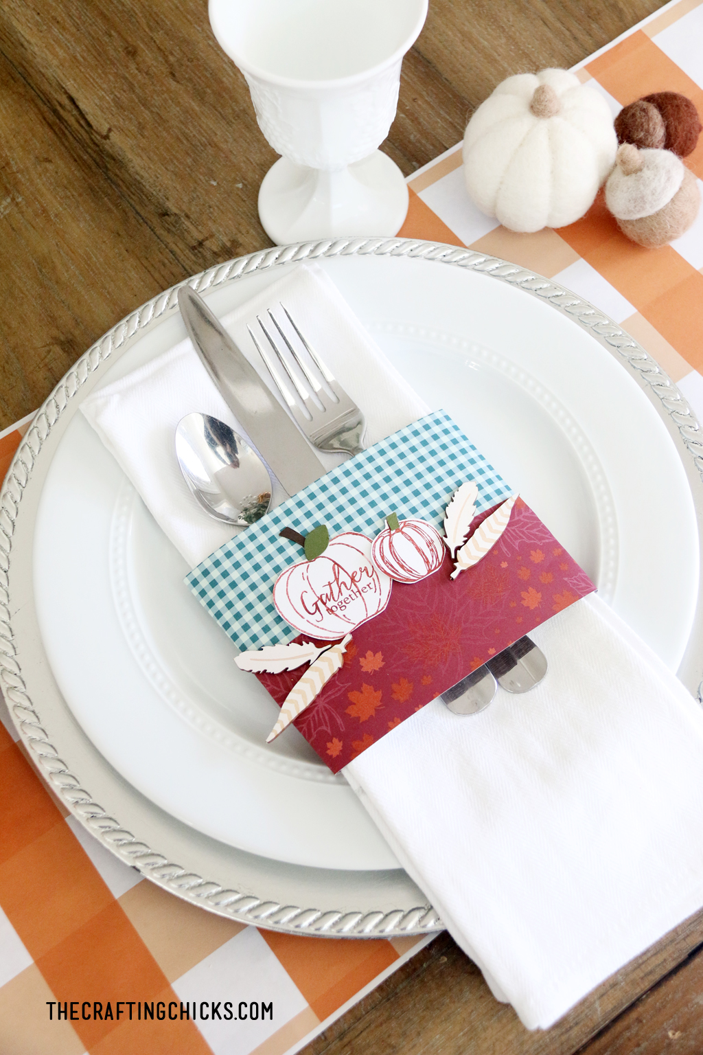 Easy Thanksgiving place setting with orange plaid place mat, white plate, and stamped napkin ring with pumpkins.