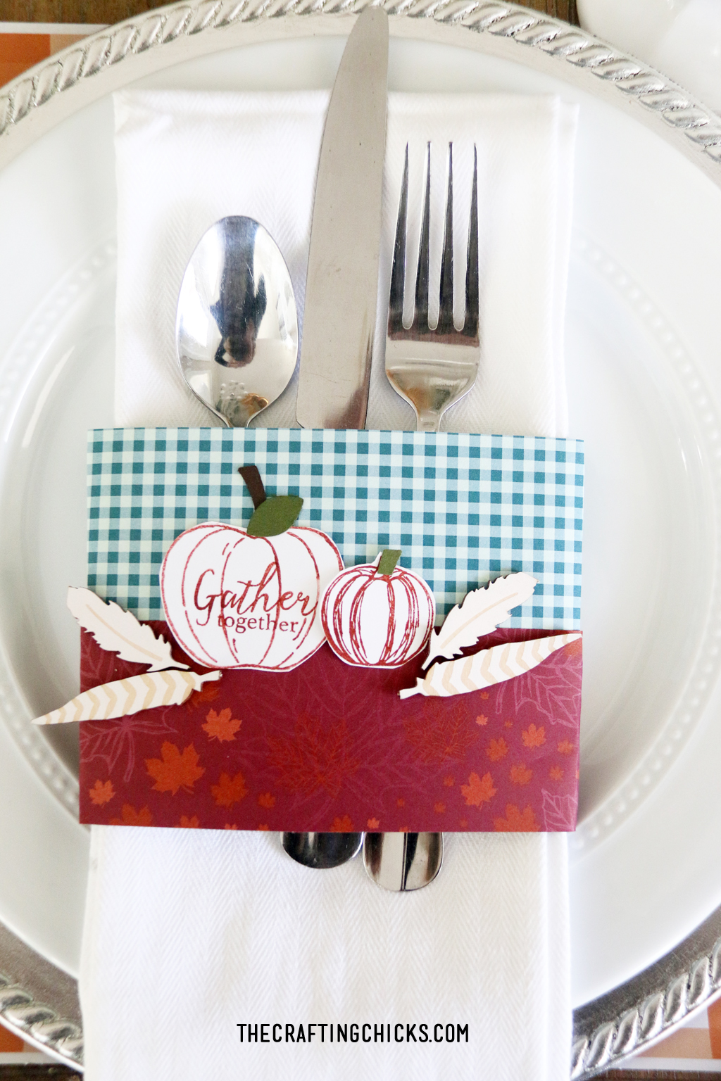 Thanksgiving place setting with orange plaid place mat, white plate, and stamped napkin ring with pumpkins.