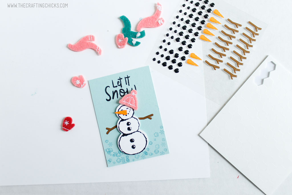 Add embellishments to the stamped snowman.