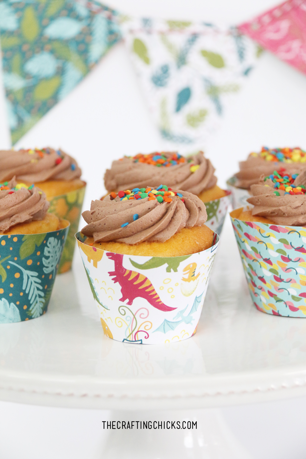 Cupcakes with chocolate frosting and DIY dinosaur cupcake paper wrappers.