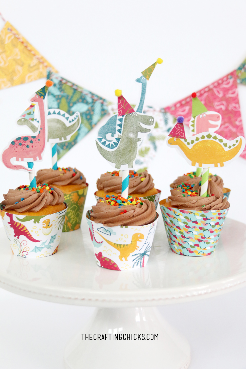Hand stamped Dinosaurs on paper straws stuck in cupcakes. Cute Dinosaur Cupcake toppers.