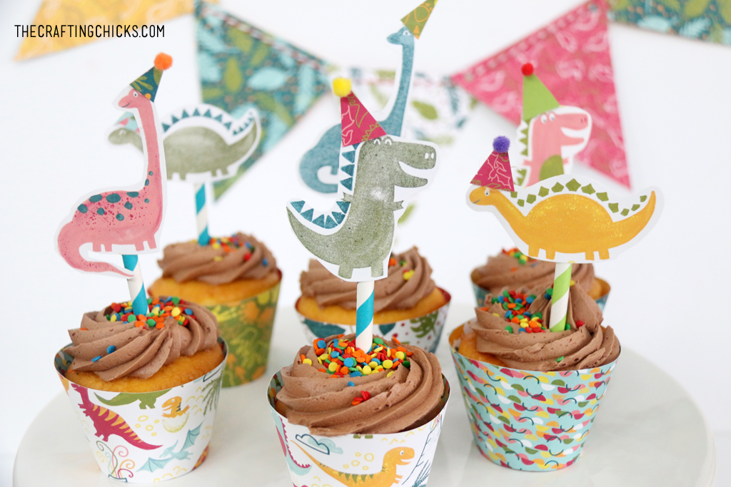 Hand stamped dinosaurs with party hats glued onto stripped paper straws for cupcake toppers.