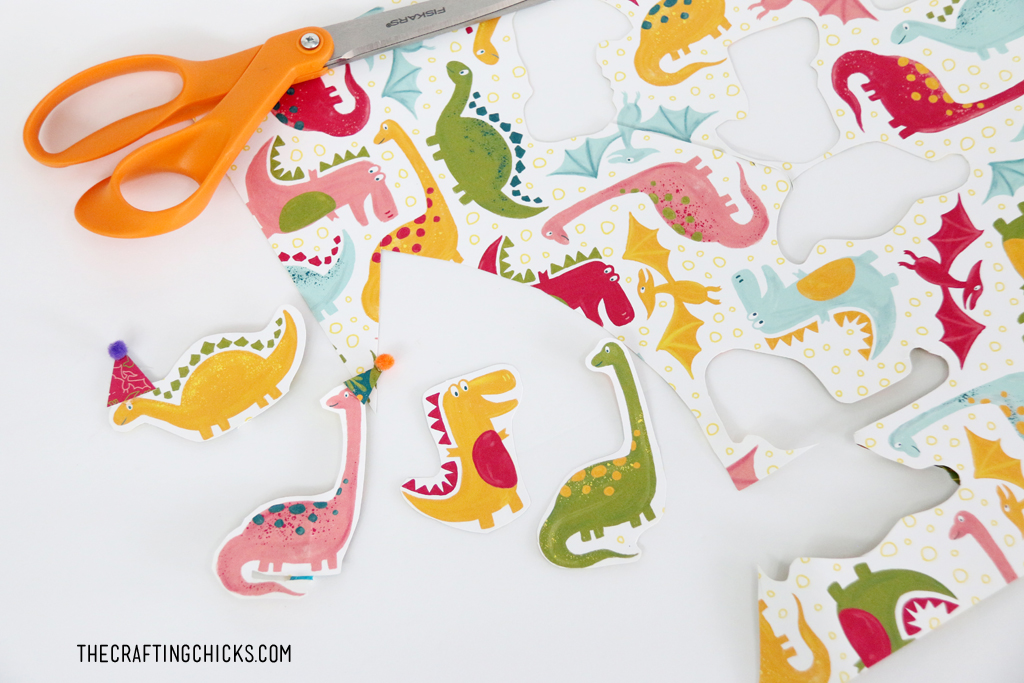 Dinosaurs cut out from scrapbook paper to make Cute Dinosaur Cupcake toppers.