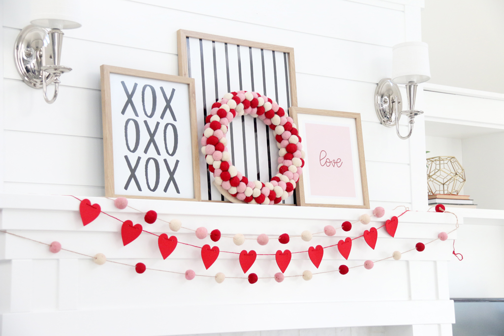 "White mantle with red heart banner and pink, red, and white pom pom banner. Three pictures in frames one with XOXO in black and white, one with black and white stripes, and one with Pink background and the word ""Love"" in red."