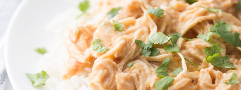 Crockpot Fiesta Ranch chicken served over white rice with cilantro sprinkled over top.