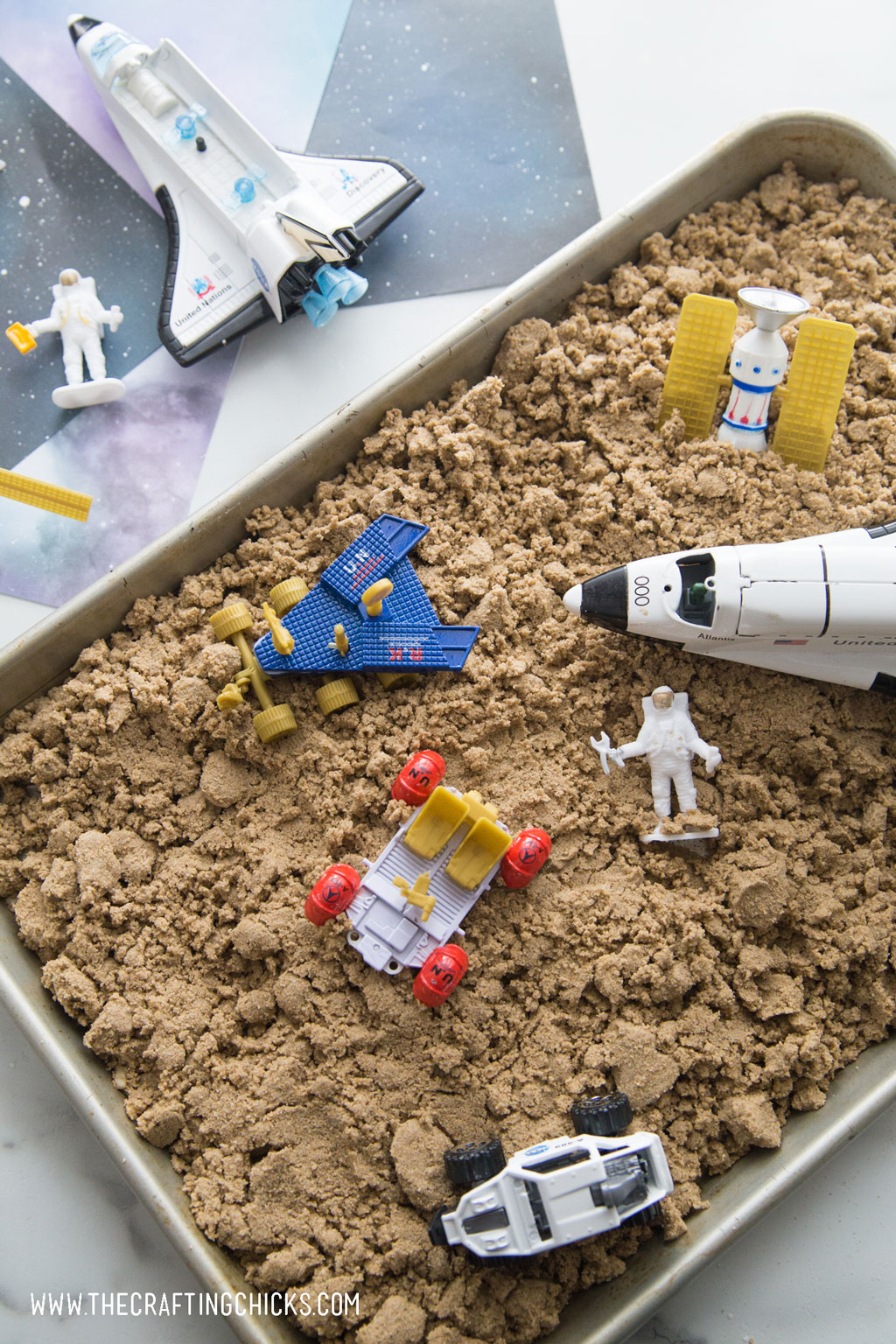Moon sand with rocket and astronaut as play toys.
