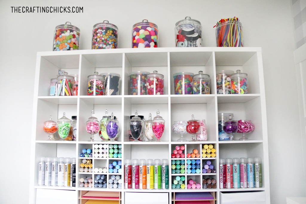 White shelves decorated with colorful jars filled with craft supplies, colorful paper, and colorful paint.