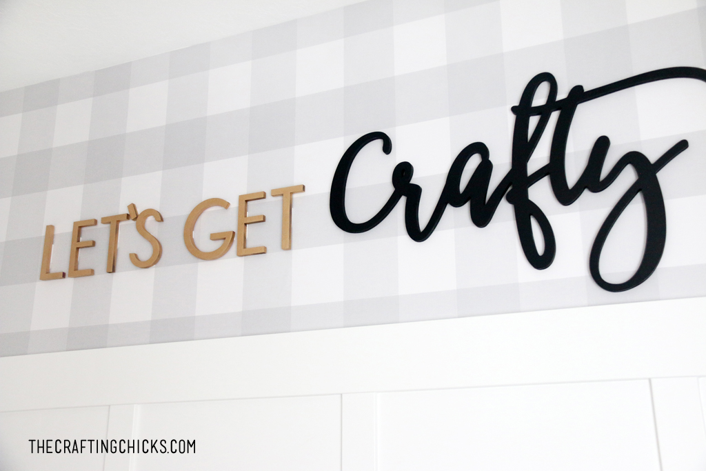 Gray plaid wallpaper on a wall with gold and black cut out letters spelling Let's Get Crafty.