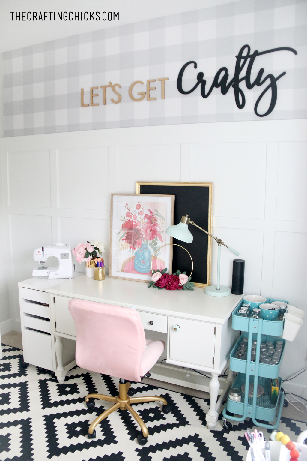 White desk with pink office chair. Floral picture and sewing machine off to the side.