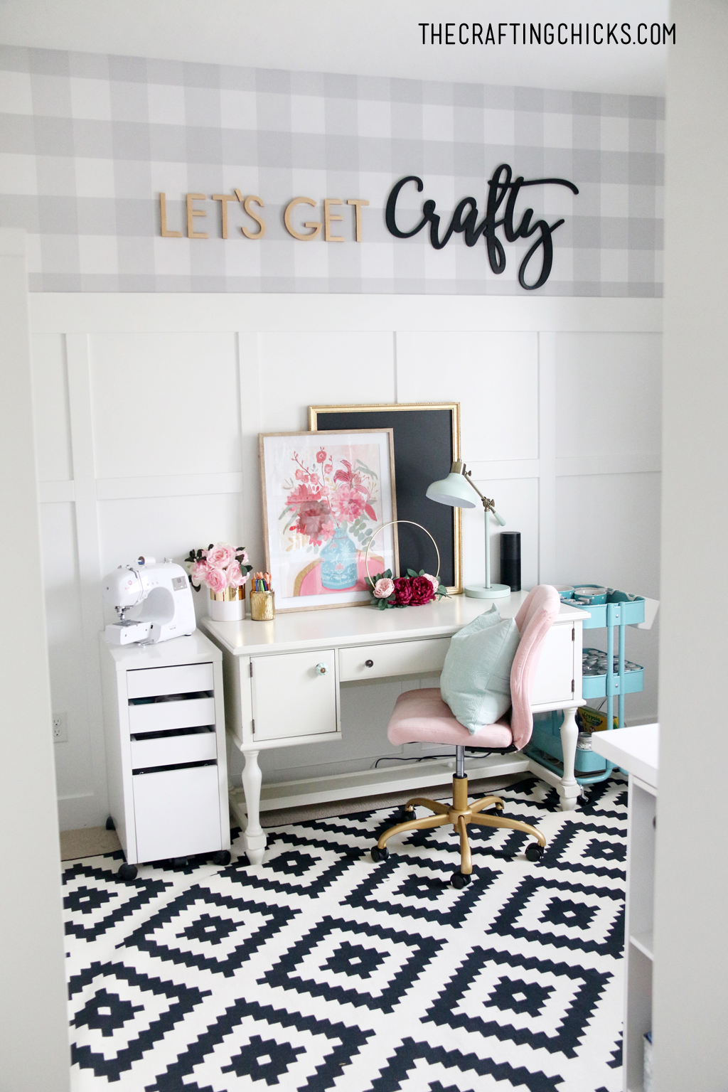 White desk with pink plush chair and sewing machine on the side. Gray and white plaid wallpaper with Let's Get Crafty wood cutout letters.