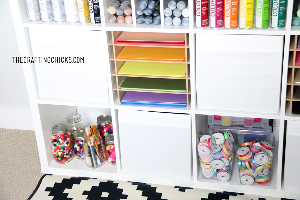 Colorful crafting supplies on a white shelf.