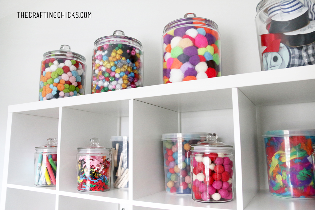 Apothecary jars filled with colorful pompoms and other crafting supplies for a craft room design