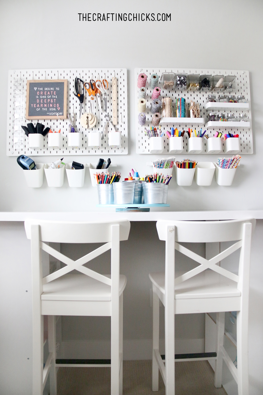 Wall with white peg board and craft supplies on it. Table and white stools in front for a crafting space.