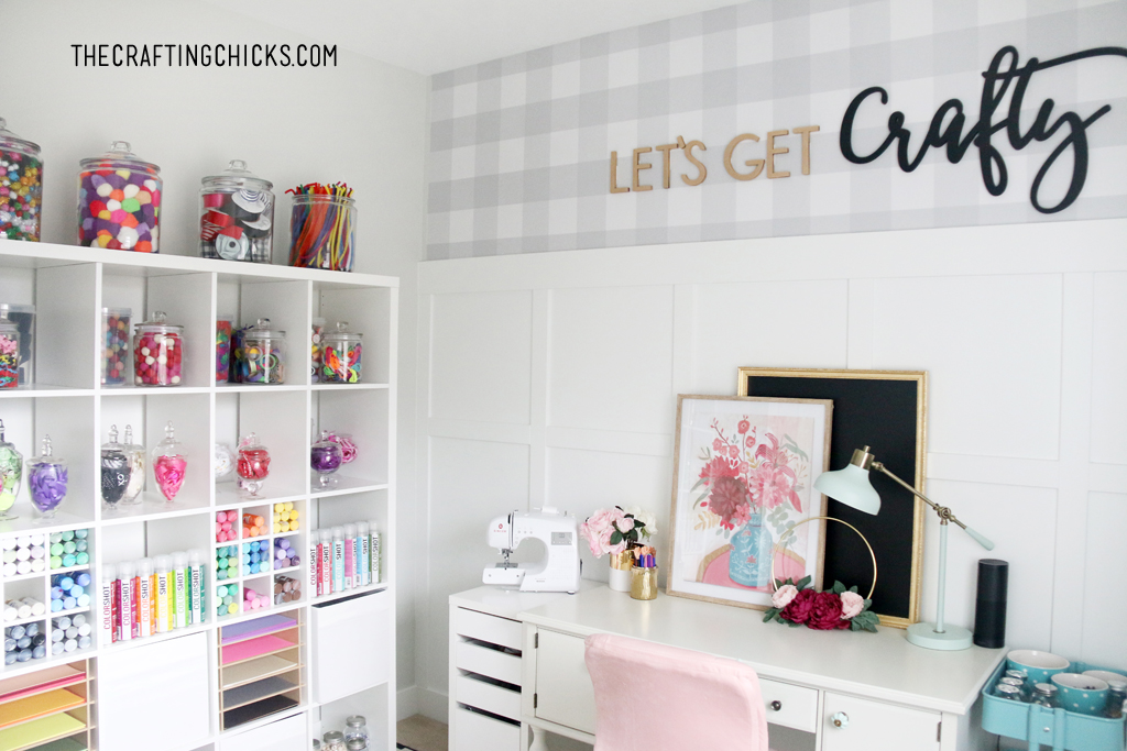 Craft room with white shelves decorated with colorful jars full of craft supplies. White desk with pink plush office chair.
