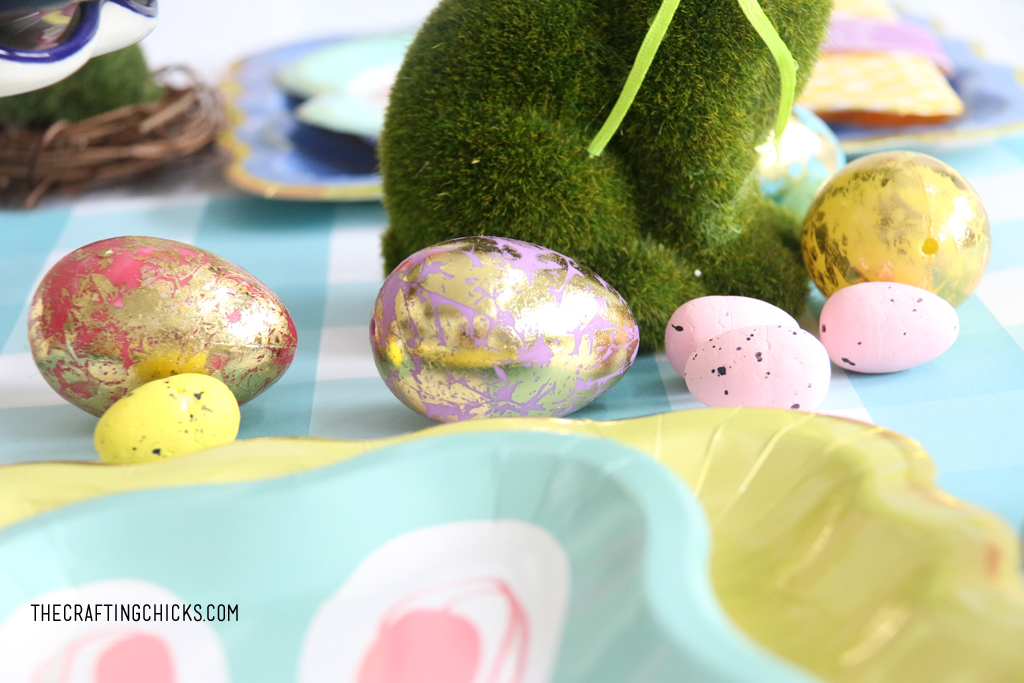 Gold foil eggs and small speckled eggs on an Easter table as decoration.