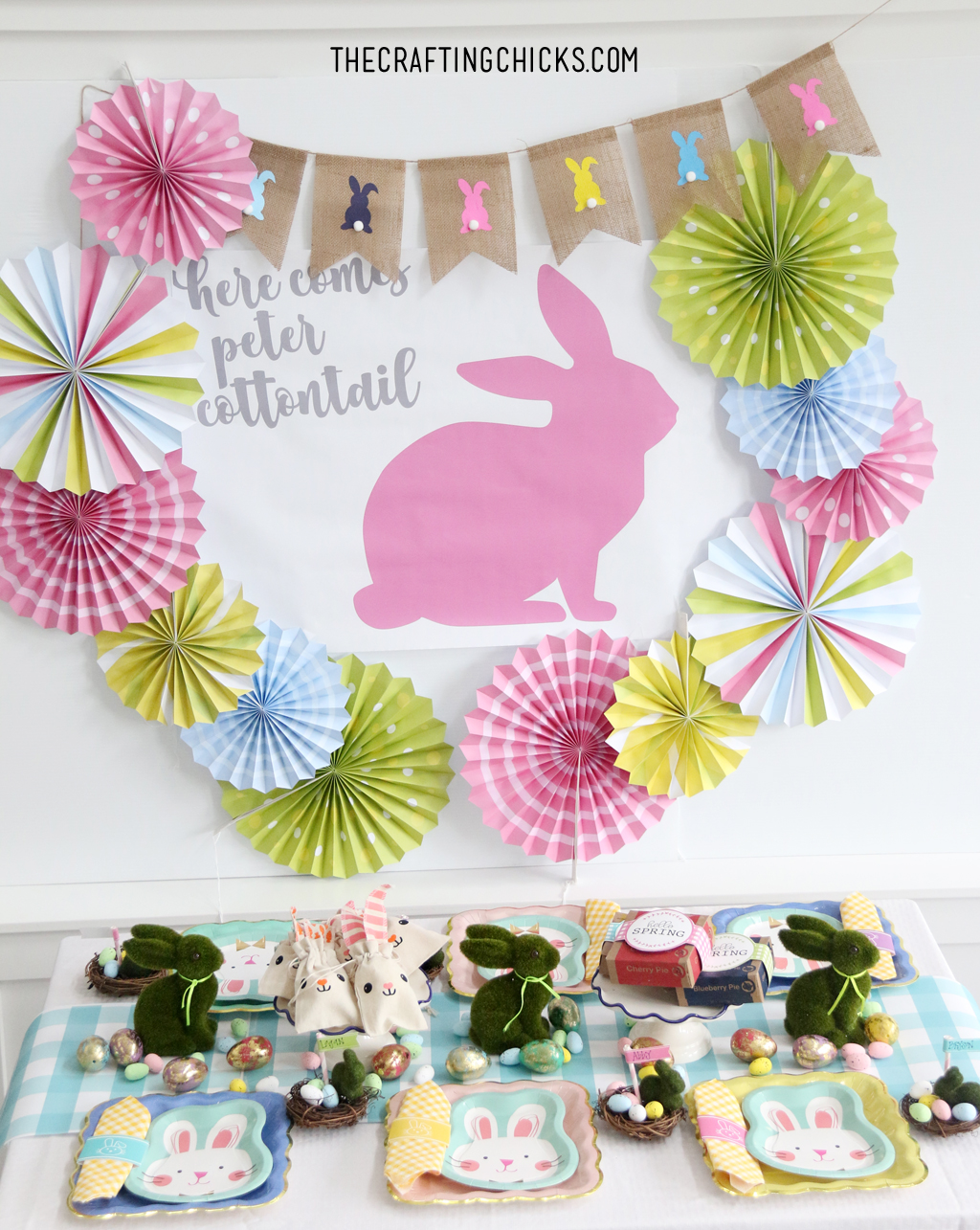 Easter table for kids with bunny paper plates, yellow gingham napkin and bunny decorations. Big Pink bunny printable backdrop