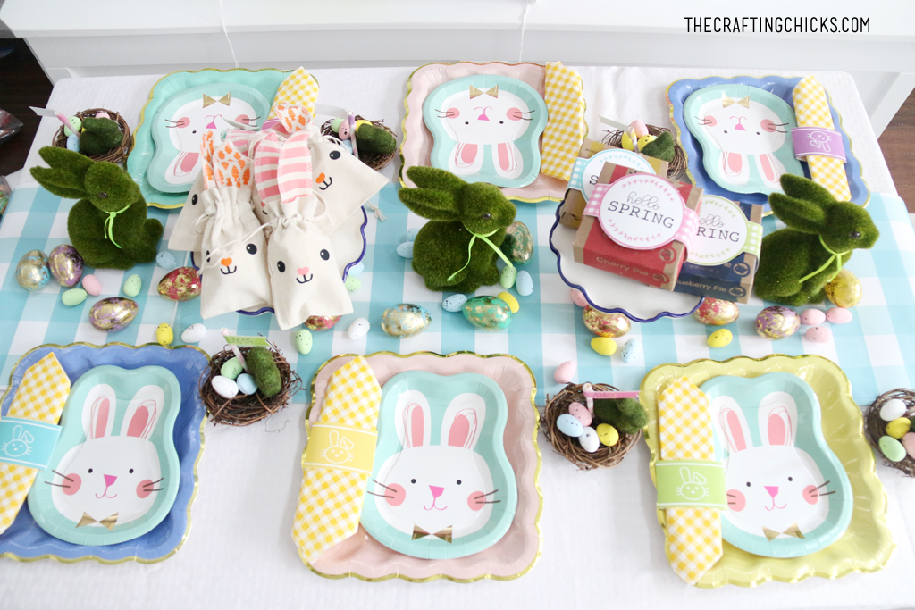 Easter table for kids with bunny paper plates, yellow gingham napkin and bunny decorations.