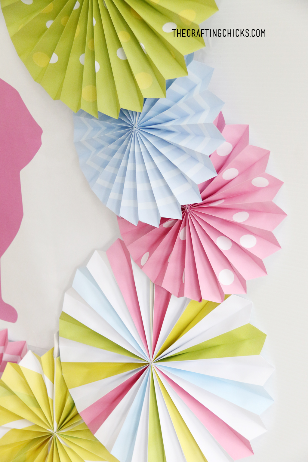 Bright colored decorative paper fans in bright green, pink, yellow and blue.