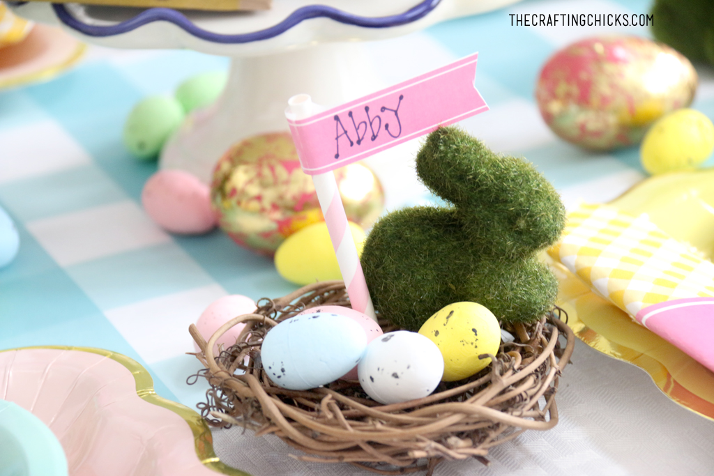 Easter table for kids with faux grass bunny decoration and faux eggs as in a nest with a name tag as table decoration.