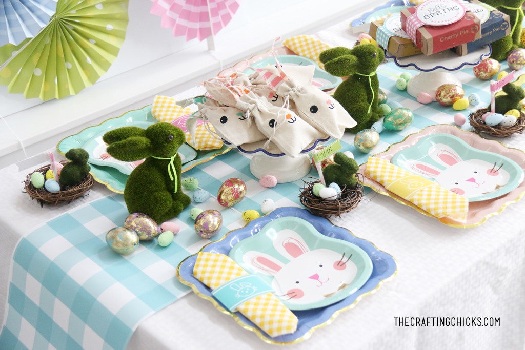 Easter table for kids with faux grass bunny decoration and faux gold foil eggs as decoration.