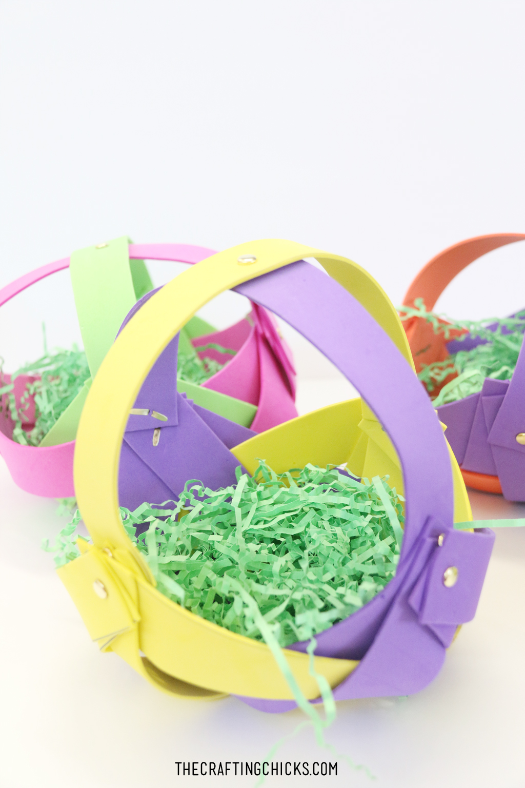 Foam strips woven together to make a basket with brads, filled with green Easter grass.