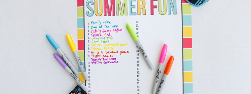 Markers and sunglasses around a poster sized printable 50 Days of Summer Fun chart