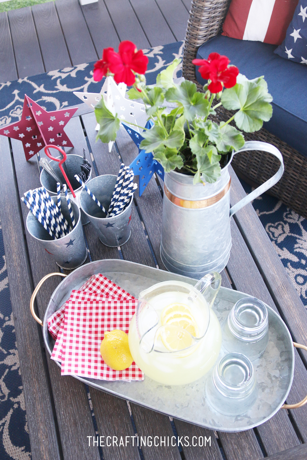 Metal Galvanized pitcher with red geraniums in front of a galvanized tray with glass pitcher of lemonade.