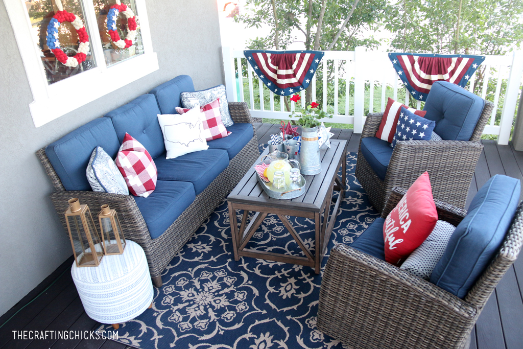 Backyard deck with dark wicker furniture and pops of red, white and blue patriotic decor.
