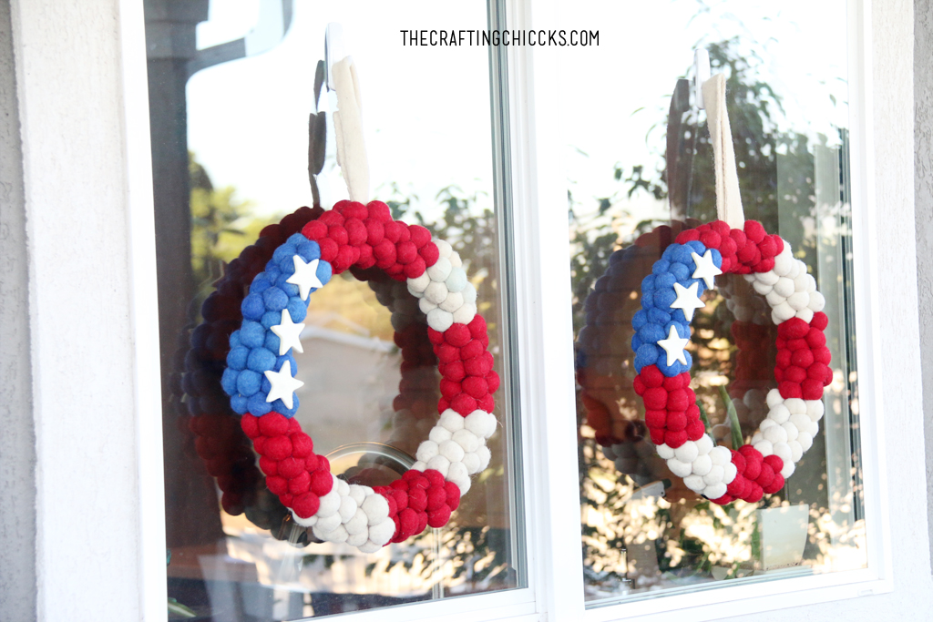 Patriotic Pom Pom wreaths hung on a window for deck decorations