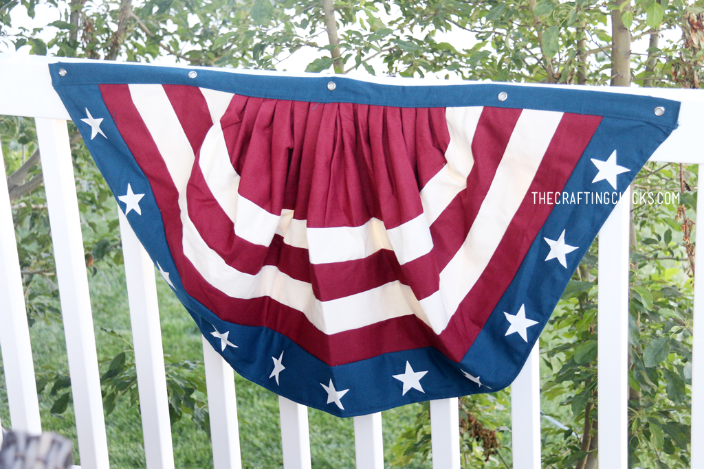 Red, white, and blue patriotic bunting on a white fence railing.