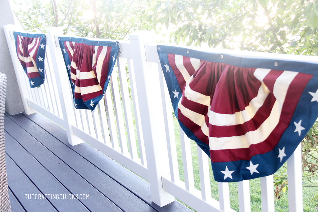 Red, white, and blue buntings hung up on the railing of a backyard deck