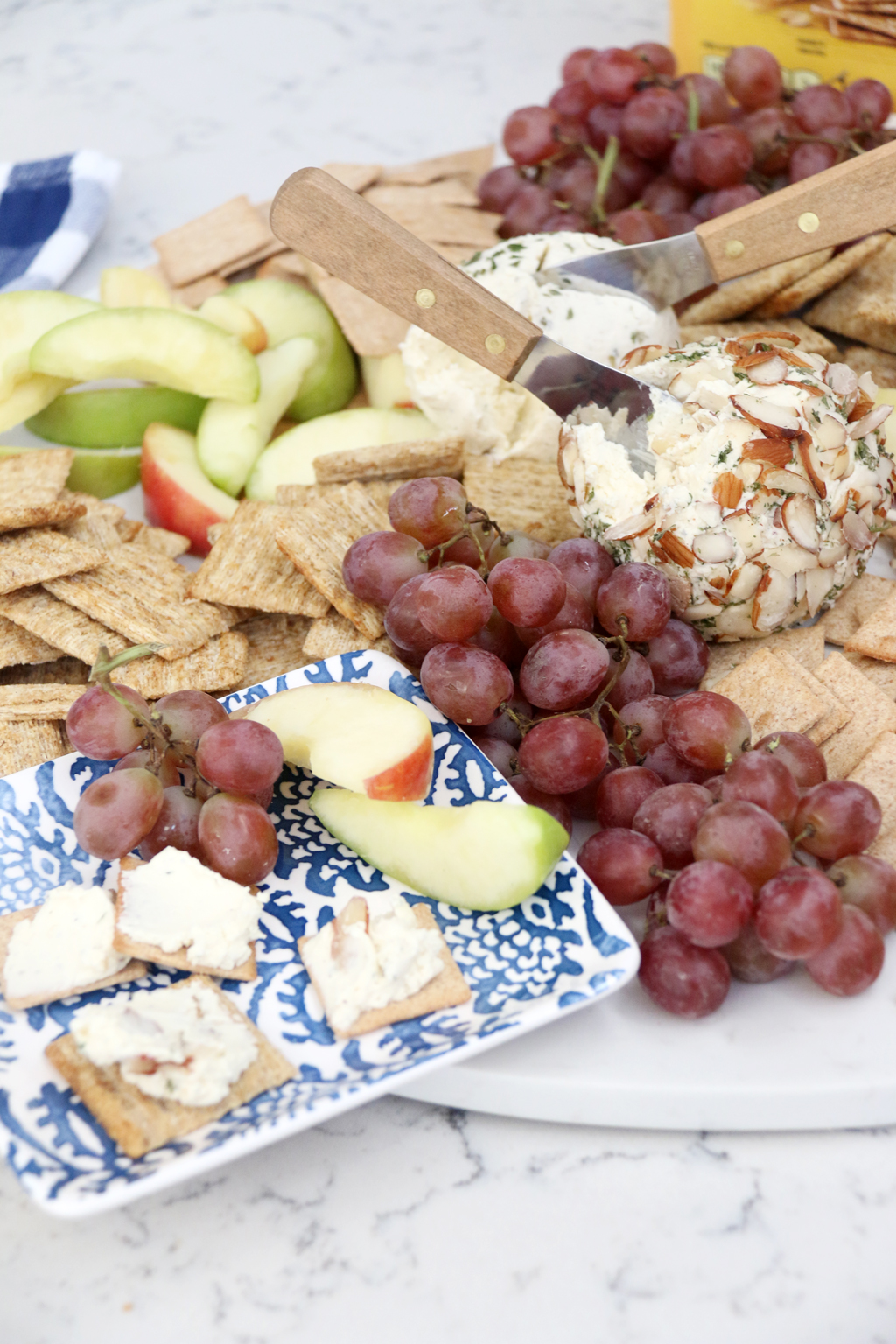 Simple Ranch Cheese Ball on crackers with grapes and apple slices.