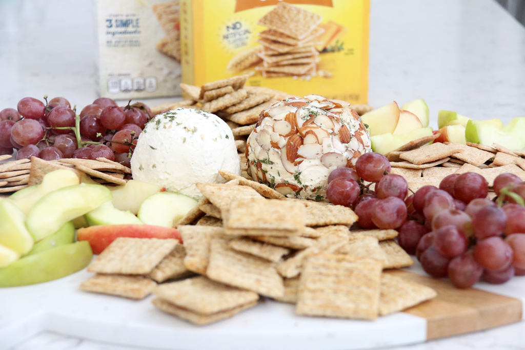 Simple Ranch Cheese Ball with crackers, apple slices, and grapes on a board.