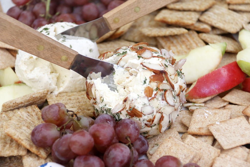 Ranch Cheese ball covered in slivered almonds on a plate with crackers.
