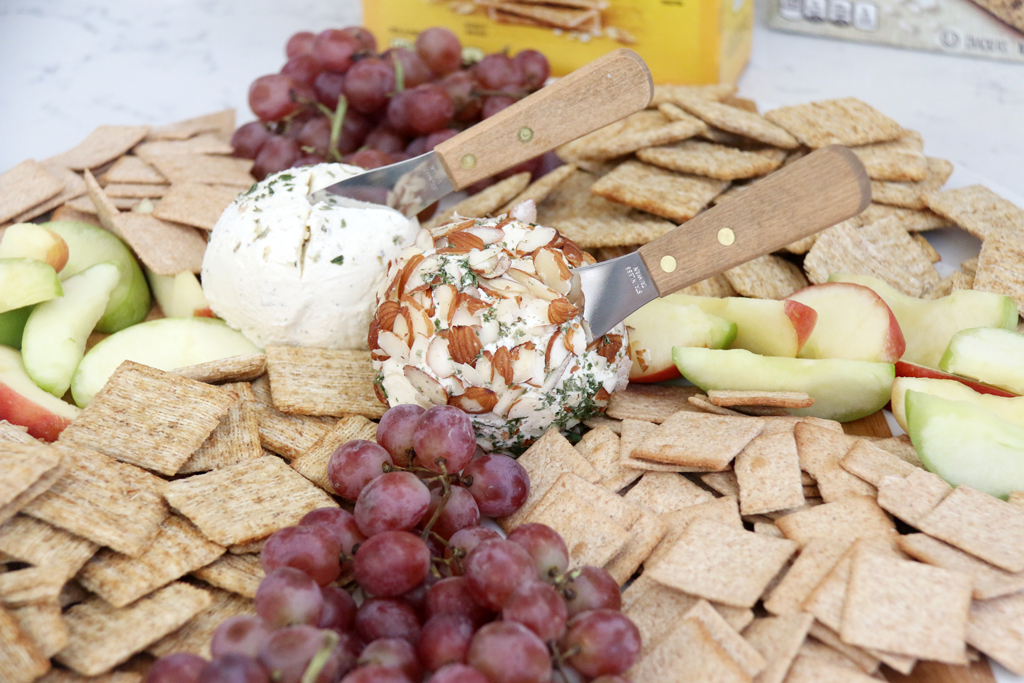 Simple ranch cheese balls one rolled in almonds on a cracker board