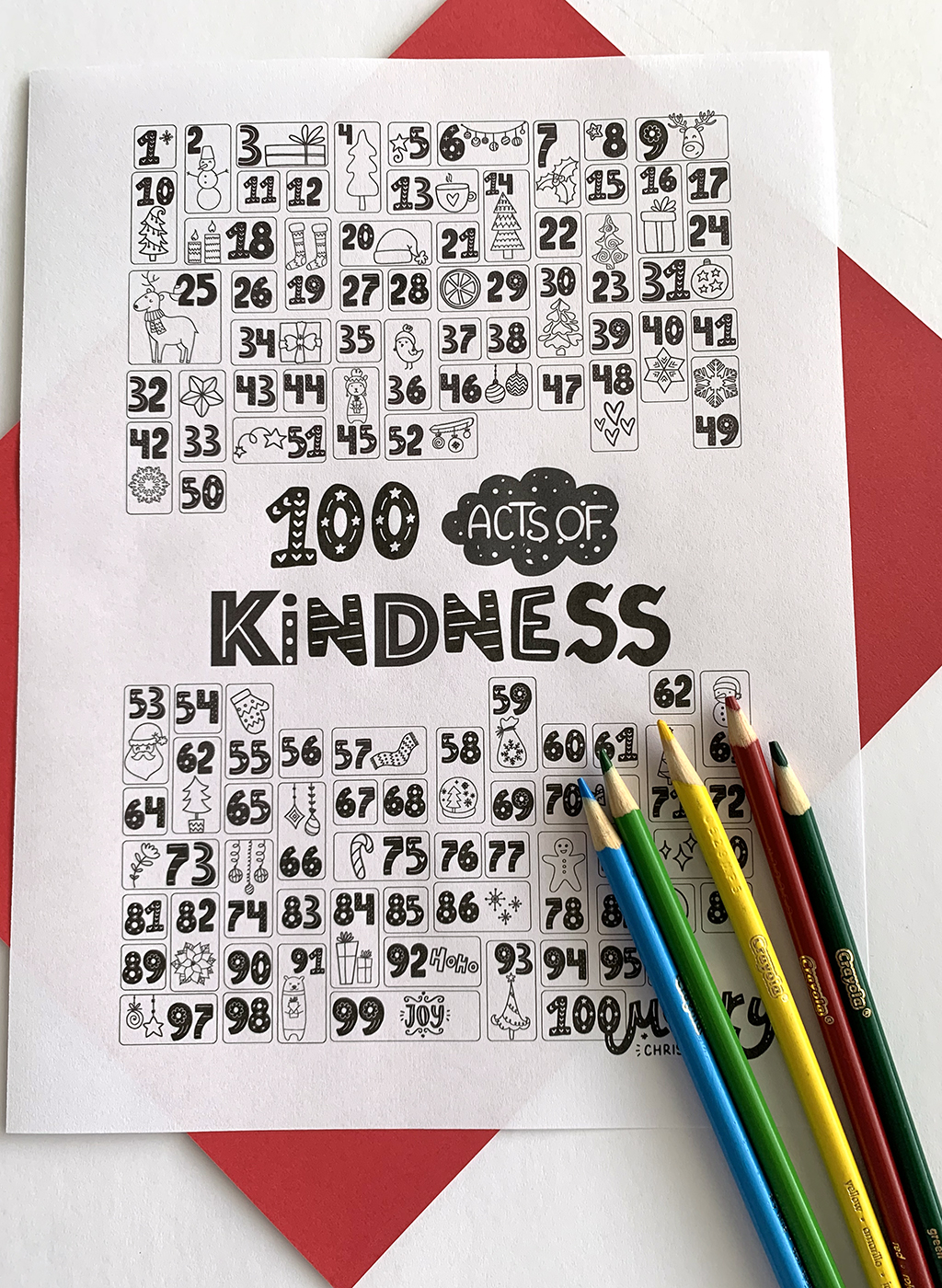 100 Acts of Kindness Coloring Countdown in black and white with a red paper under neath the print out and some colored pencils.