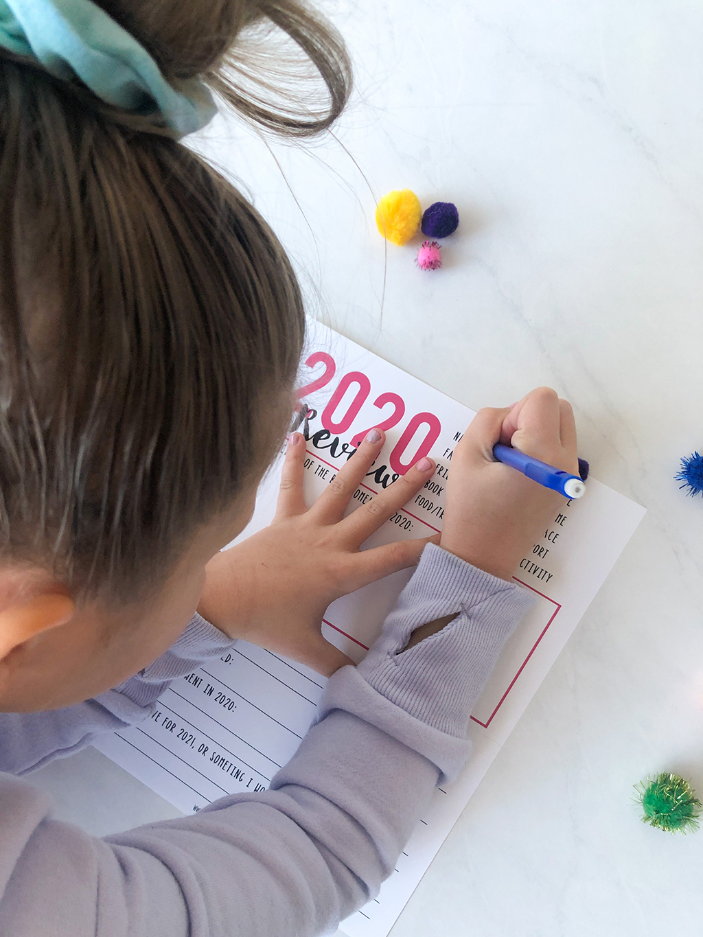 Little girl using a pencil to fill in a 2020 Year in Review printable with pink type.