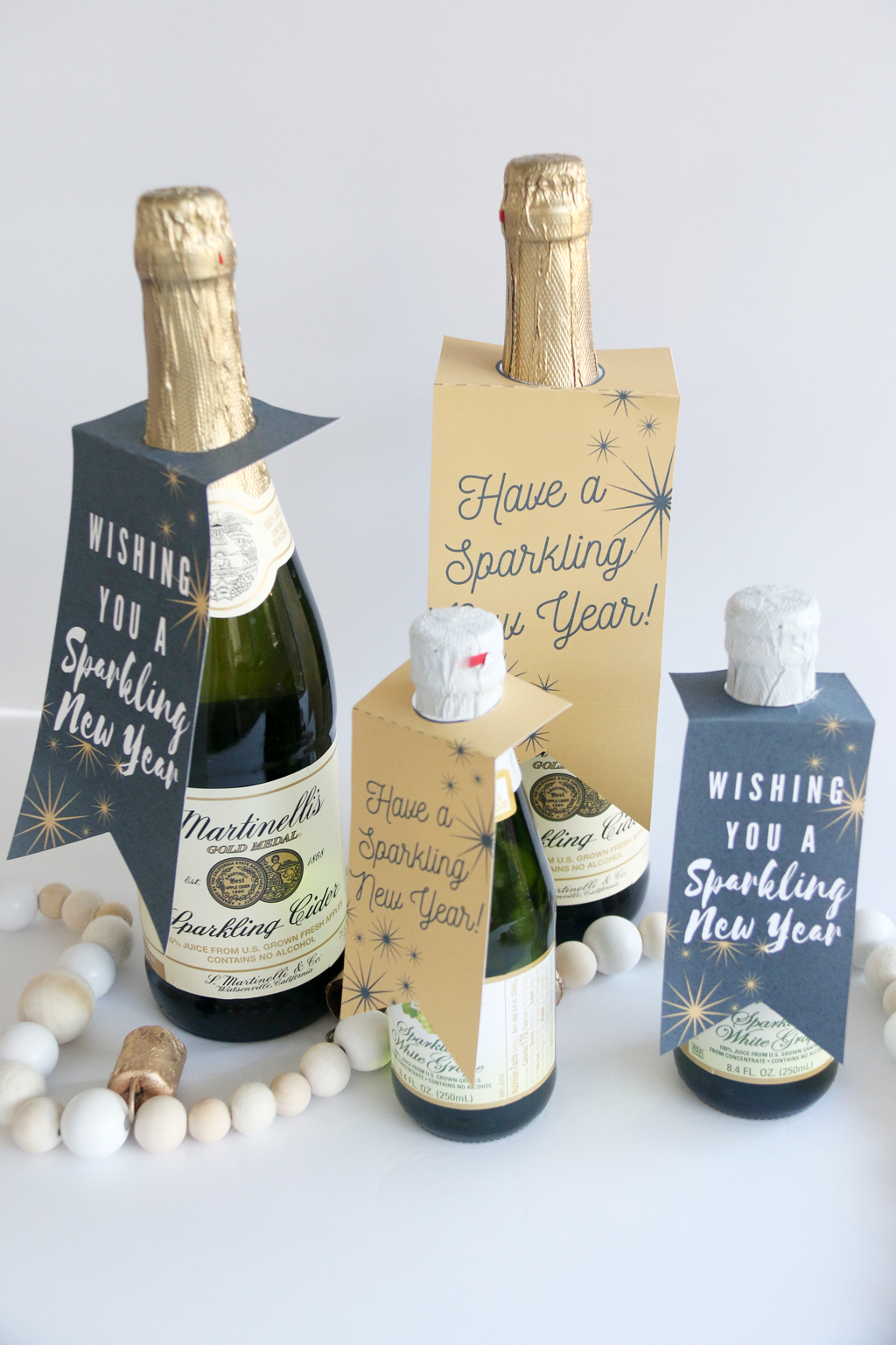 Large and small bottles of sparkling cider with New Year Sparkling Cider Gift Tags on them
