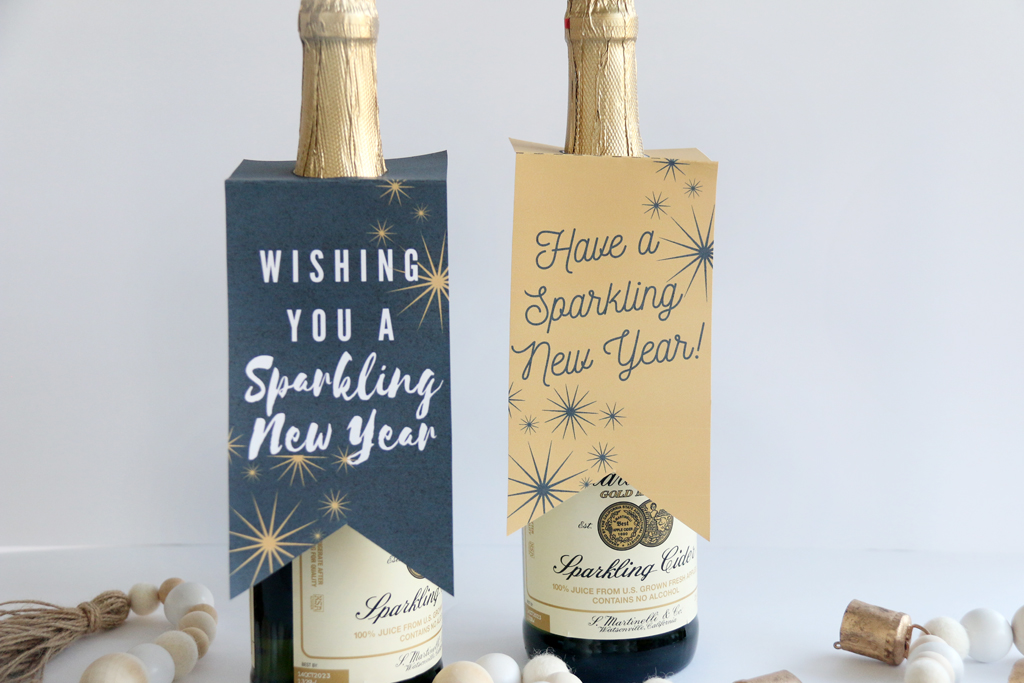 Two large bottles of sparkling cider with gift tags on them