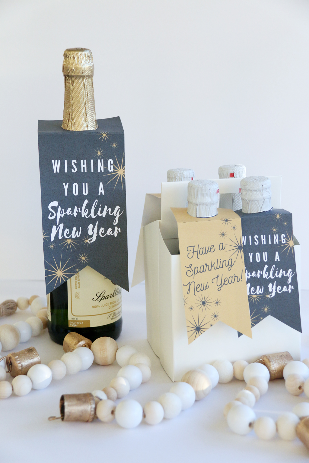 One large and drink caddy full of small bottles of Sparkling cider with New Year Sparkling Cider Gift Tags