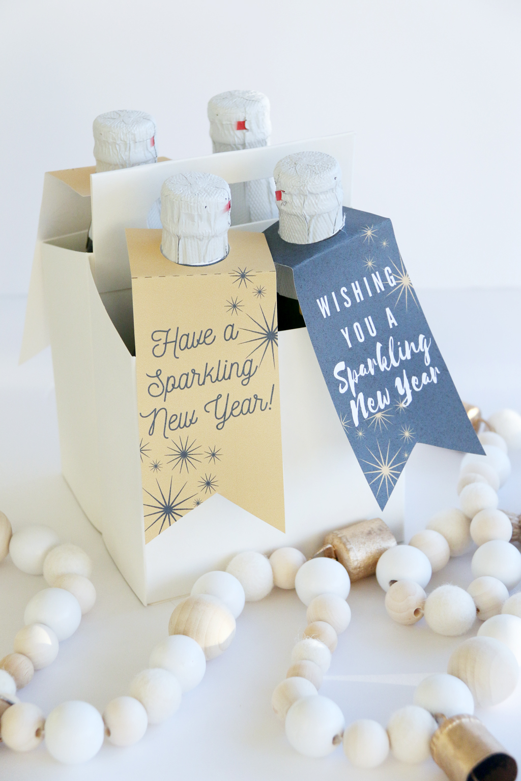 Small drink caddy filled with 4 bottles of sparkling cider with gift tags on them.