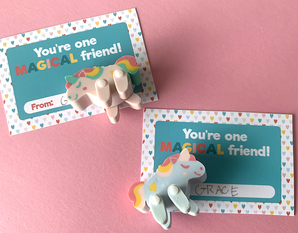 Pink and green unicorn movable erasers on free printable valentines staged on a pink background